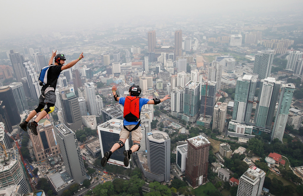 Description of . Base jumper Kieran Olivier Julien Chacornac, right, and Christian Gomis of France leap from the 300-meter Open Deck of the Malaysia's landmark Kuala Lumpur Tower during the International Tower Jump in Kuala Lumpur, Friday, Sept. 27, 2013. (AP Photo/Vincent Thian)
