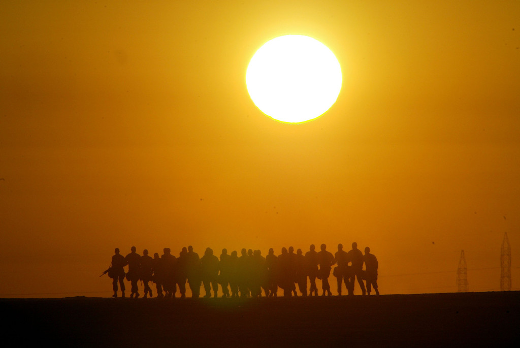 Description of . United States Marines from the 1st Marine Division run laps around their camp early in the morning February 17, 2003 near the Iraqi border in Kuwait. The Marines were preparing for a possible military strike against Iraq. (Photo by Joe Raedle/Getty Images)