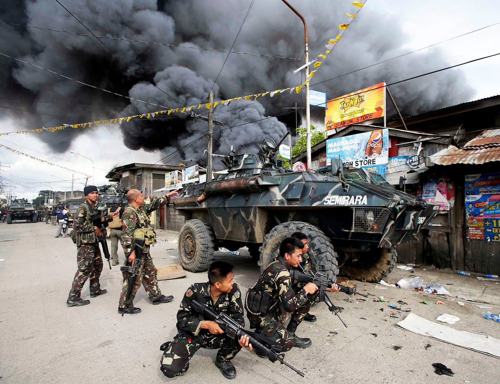 Description of . Government troopers continue their assault on Muslim rebels Thursday, Sept. 12, 2013, at Zamboanga city in the southern Philippines.  Philippine troops battled Muslim rebels on two fronts Thursday, after extremists attacked a second city near the southern port where guerrillas have been holding scores of residents hostage in a four-day standoff with government forces. (AP Photo/Bullit Marquez, File)