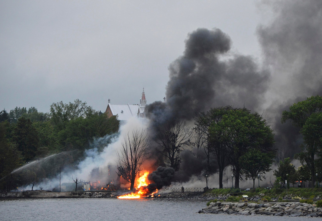 Description of . The town continues to burn following a train derailment and explosion in Lac Megantic, Quebec, early July 6, 2013. REUTERS/Jean Gauthier