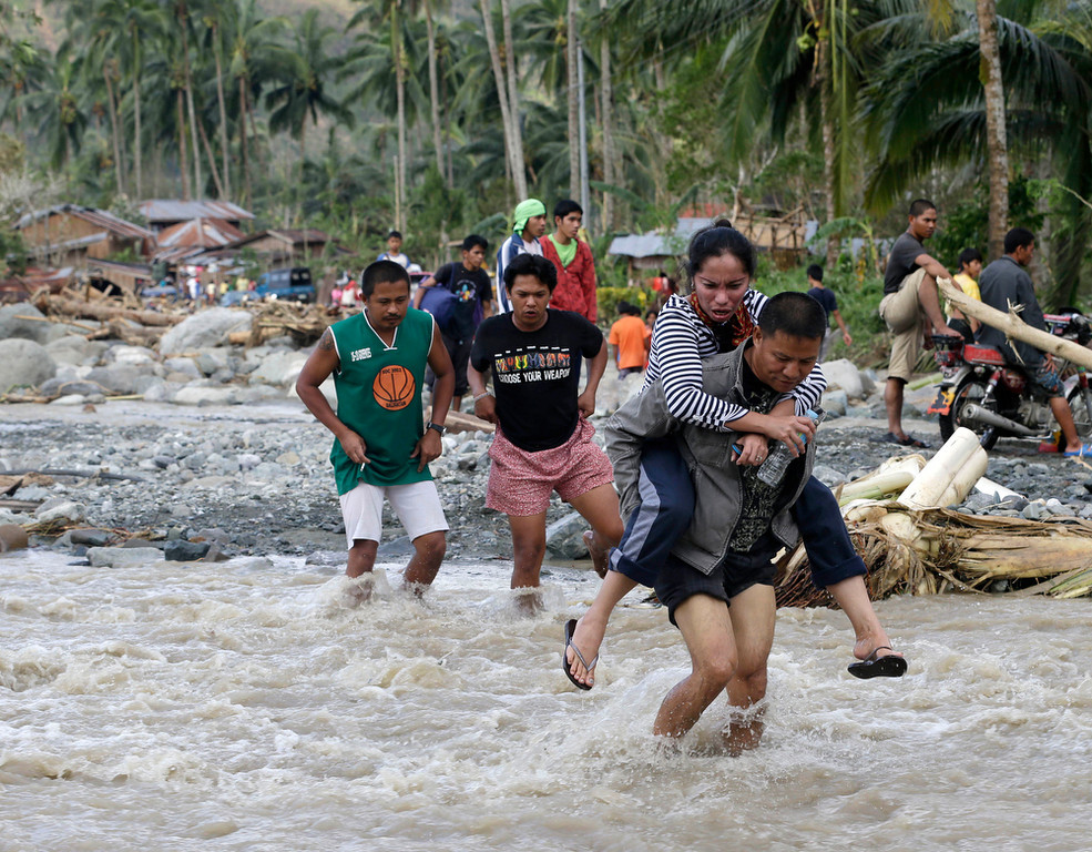 Description of . Residents cross a river in the flash flood-hit village of Andap, New Bataan township, Compostela Valley in southern Philippines Wednesday, Dec. 5, 2012.  Typhoon Bopha, one of the strongest typhoons to hit the Philippines this year, barreled across the country\'s south on Tuesday, killing scores of people while triggering landslides, flooding and cutting off power in two entire provinces. (AP Photo/Bullit Marquez)