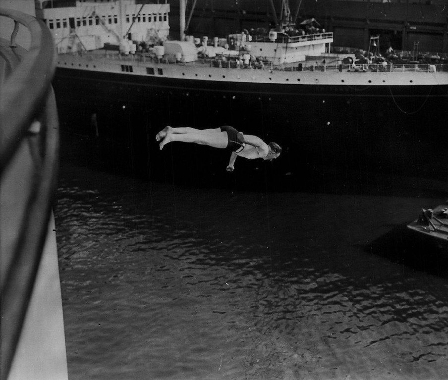 Description of . Edgar Foster, a 56-year-old Brit, dives into the North River from the sundeck of the Queen Elizabeth in a carefully planned stunt on Jul. 16, 1953.