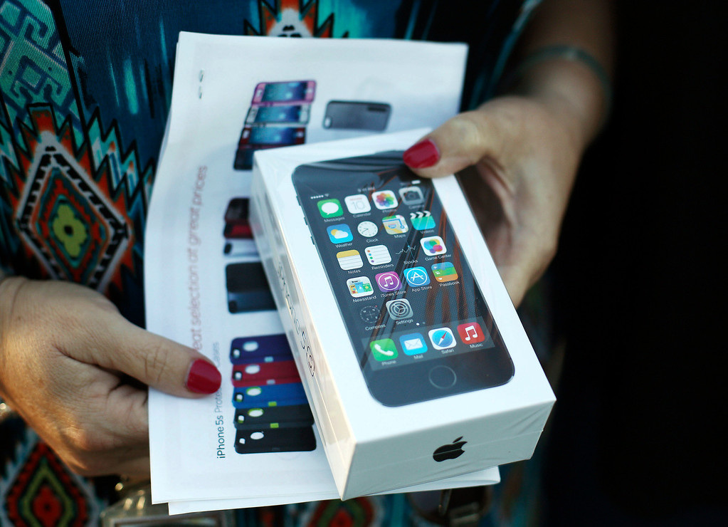 Description of . JoAnn Dulaney displays a new iPhone 5s sold in Pembroke Pines, Fla., Friday, Sept. 20, 2013. Dulaney stood in line for 13 hours to buy the phone for her son. (AP Photo/J Pat Carter)