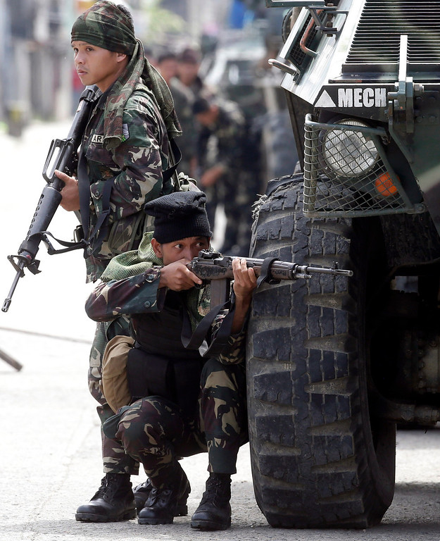 Description of . A Government trooper aims his rifle in a continuing operation to rescue scores of hostages being used as human shields by Muslim rebels on the fourth straight day Thursday, Sept. 12, 2013 at Zamboanga city in southern Philippines. (AP Photo/Bullit Marquez)