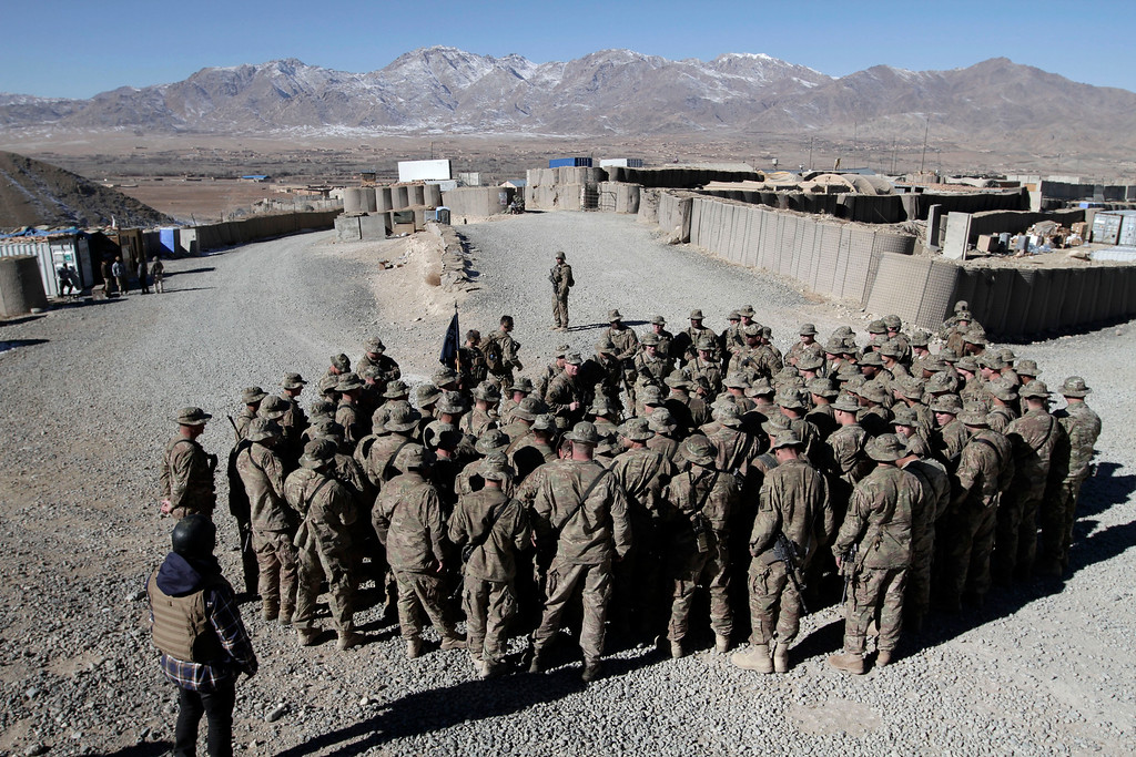 Description of . U.S. troops gather to talk to Maj. Gen. James C. McConville during his Christmas visit to Wardak province, eastern Afghanistan, Wednesday, Dec. 25, 2013. The commander of NATO forces in eastern Afghanistan spent Christmas visiting U.S. troops at bases across the mountainous region to bring them holiday greetings and gifts for a few lucky soldiers.(AP Photo/Rahmat Gul)
