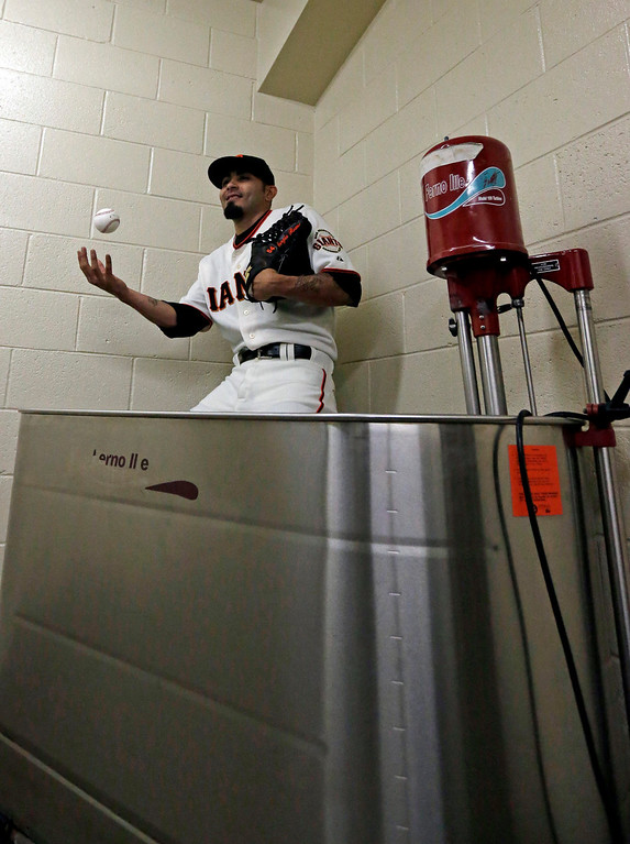 Description of . San Francisco Giants' Sergio Romo poses for a picture in a hot tub during baseball spring training photo day Wednesday, Feb. 20, 2013  in Scottsdale, Ariz. (AP Photo/Morry Gash)