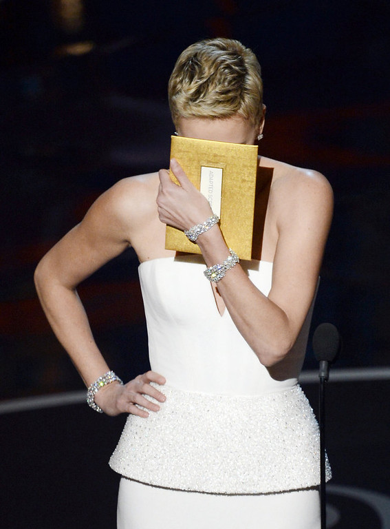 Description of . Actress Charlize Theron reacts as she presents onstage during the Oscars held at the Dolby Theatre on February 24, 2013 in Hollywood, California.  (Photo by Kevin Winter/Getty Images)