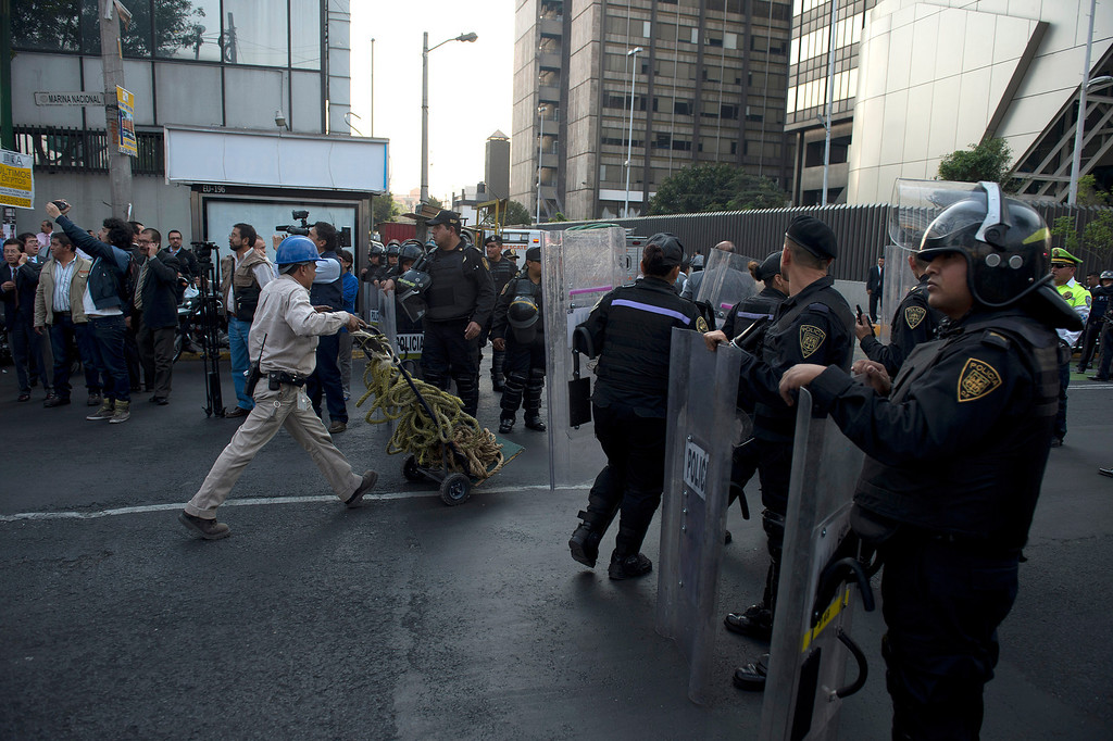 Description of . Police stand guard as a rescue team heads for the skyscraper that houses the headquarters of state-owned Mexican oil giant Pemex in Mexico City on January 31, 2013, following a blast inside the building. An explosion rocked the skyscraper, killing at least 14, as a plume of black smoke billowed from the 54-floor tower, according to official sources.   YURI CORTEZ/AFP/Getty Images