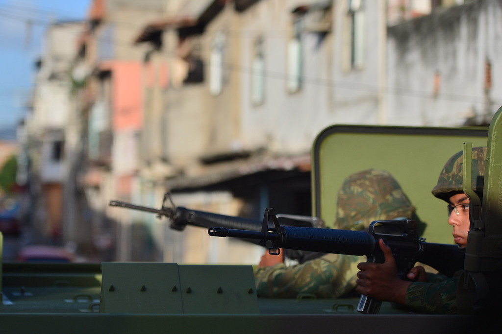 Description of . Brazilian soldiers patrol the street during security operations in Vila Pinheiro --part of the Mare shantytown complex near the Galeao (Antonio Carlos Jobim) international airport-- in the north suburb of Rio de Janeiro on April 5, 2014. Thousands of soldiers --including some 2,000 paratroopers, 450 sailors and 200 military police-- in armored vehicles, trucks and on foot entered one of Rio de Janeiro's most notorious slums to provide security less than three months before the World Cup and until July 30. CHRISTOPHE SIMON/AFP/Getty Images
