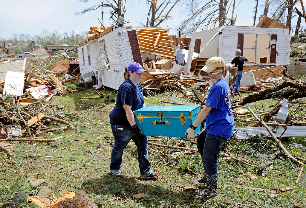 Description of . Jodi Walker and Tabitha Russell carry a trunk from a destroyed home on Clayton Avenue in Tupelo, Miss., Tuesday, April 29, 2014.  (AP Photo/Thomas Graning)