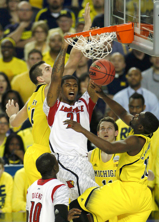 Description of . Louisville Cardinals forward Chane Behanan (C) dunks the ball between Michigan Wolverines forward Mitch McGary (L) and guard Tim Hardaway Jr. (R) in their NCAA men\'s Final Four championship basketball game in Atlanta, Georgia April 8, 2013. REUTERS/Tami Chappell