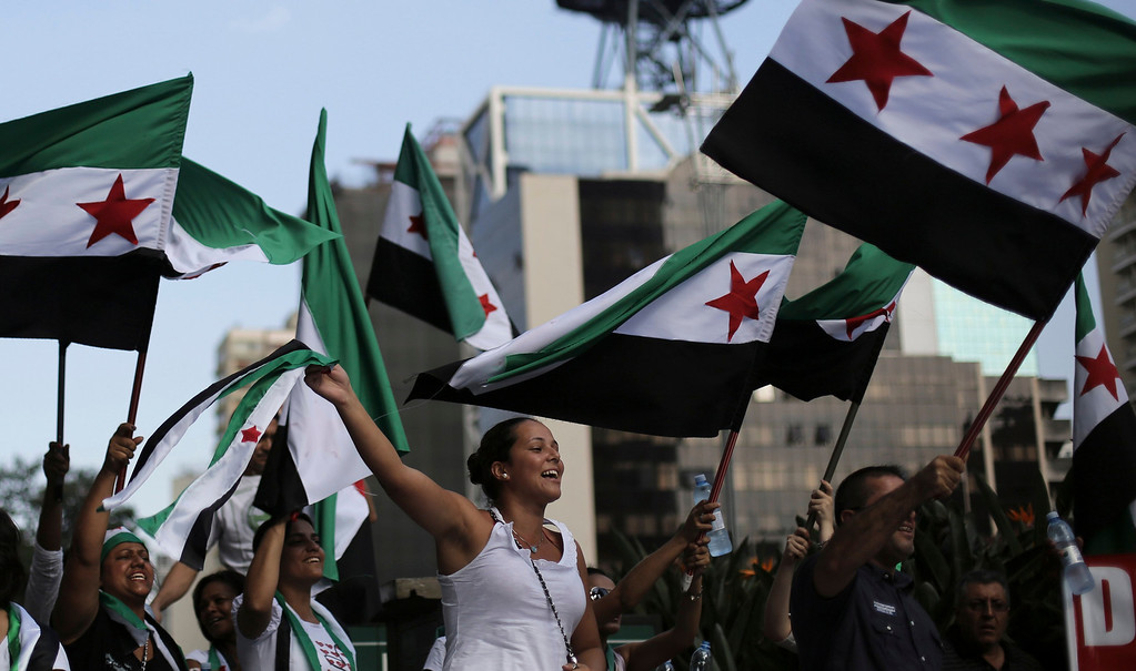 Description of . Protesters shout slogans against Syria's President Bashar al-Assad as they wave Syrian opposition flags during a protest marking two years since the start of the uprising, at Avenida Paulista in Sao Paulo March 15, 2013. REUTERS/Nacho Doce