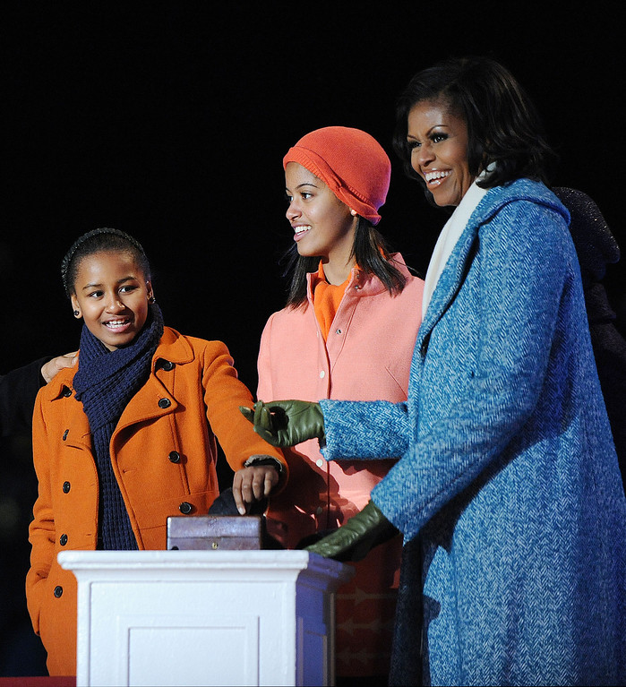 Description of . First lady Michelle Obama (R) and their daughters Malia (C) and Sasha Obama light the 90th National Christmas Tree during the Lighting Ceremony on the Ellipse behind the White House on December 6, 2012 in Washington, DC. This year is the 90th annual National Christmas Tree Lighting Ceremony. (Photo by Olivier Douliery-Pool/Getty Images)