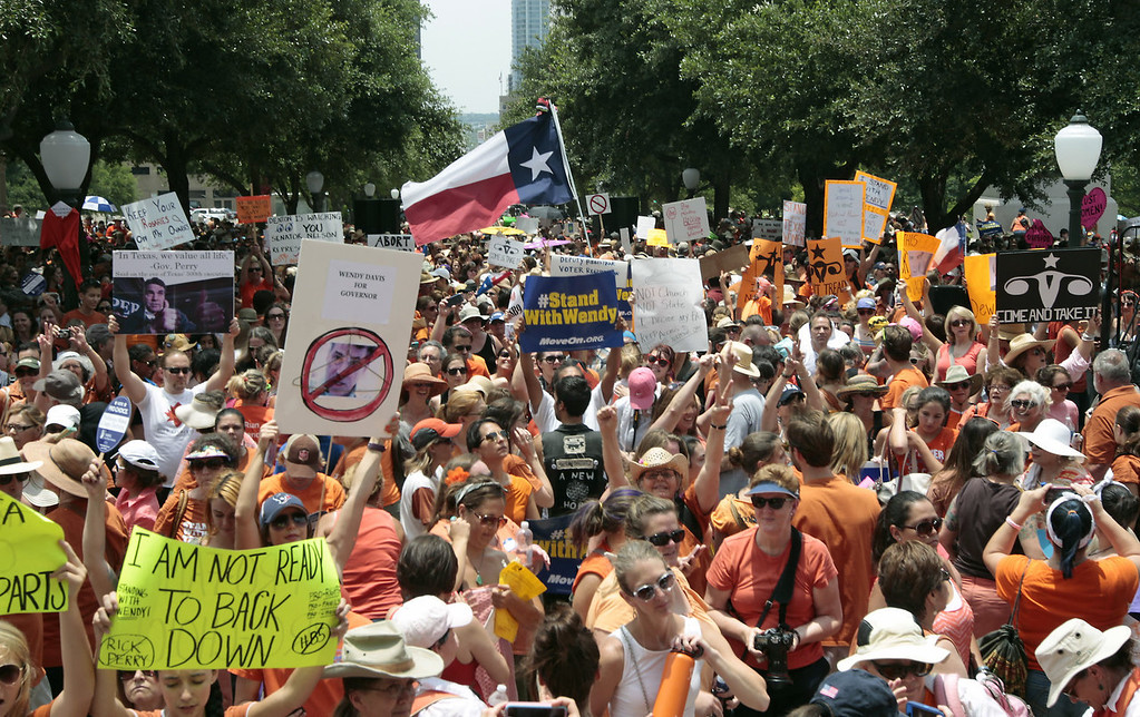 Description of . People rally in support of Texas women's right to reproductive decisions at the Texas State capitol on July 1, 2013 in Austin, Texas. This is first day of a second legislative special session called by Texas Gov. Rick Perry to pass a restrictive abortion law through the Texas legislature. The first attempt was defeated after opponents of the law were able to stall the vote until after the first special session had ended.  (Photo by Erich Schlegel/Getty Images)