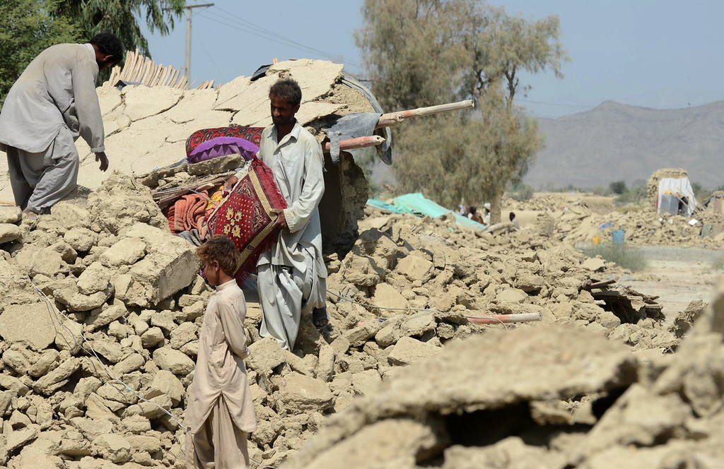 Description of . Pakistani survivors search for household items in the the debris of their destroyed houses in the earthquake-devastated district of Awaran on September 25, 2013.   AFP PHOTO/Banaras KHAN/AFP/Getty Images