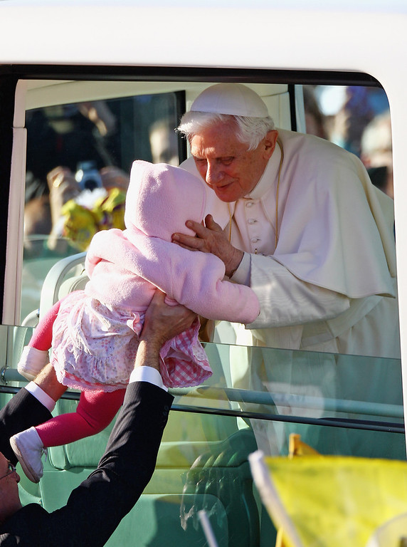 Description of . Pope Benedict XVI has announced that he is to resign on February 28, 2013 GLASGOW, UNITED KINGDOM - SEPTEMBER 16: Pope Benedict XVI kisses a young child as he arrives for the Papal Mass at Bellahouston Park on September 16, 2010 in Glasgow, Scotland. Pope Benedict XVI is conducting the first state visit to the UK by a Pontiff. During the four day visit Pope Benedict will celebrate mass, conduct a prayer vigil as well as beatify Cardinal Newman at an open air mass in Cofton Park. His Holiness will meet The Queen as well as political and religious representatives.  (Photo by Jeff J Mitchell/Getty Images)