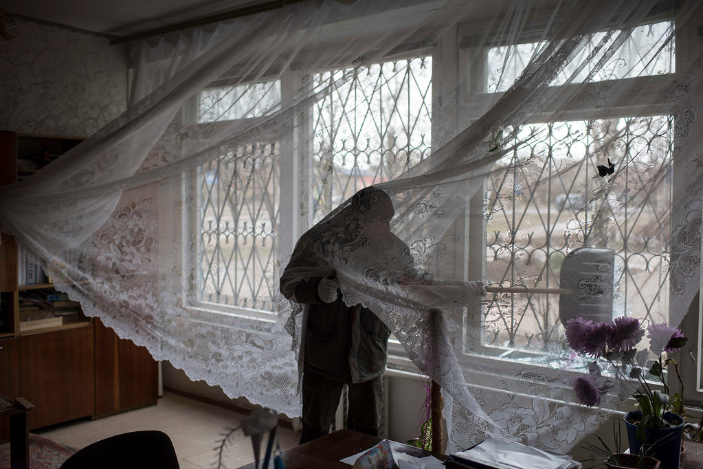 Description of . A man tries to remove pieces of broken glass from a window in a school damaged by a Grad missile in Vostochniy district of Mariupol, Eastern Ukraine, Sunday, Jan. 25, 2015. Indiscriminate rocket fire slammed into a market, schools, homes and shops Saturday in Ukraine's southeastern city of Mariupol, killing at least 30 people, authorities said. The Ukrainian president called the blitz a terrorist attack and NATO and the U.S. demanded that Russia stop supporting the rebels. (AP Photo/Evgeniy Maloletka)
