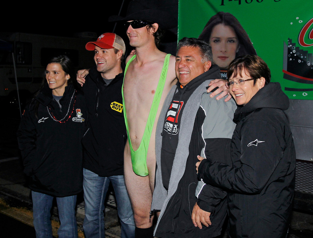 Description of . NASCAR drivers Danica Patrick, left, and Ricky Stenhouse Jr., second from left, pose with fans, including Landon Destefano, center, of Olive Branch, Miss., after she awarded the