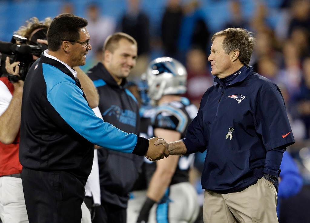 . Carolina Panthers head coach Ron Rivera, left, greets New England Patriots head coach Bill Belichick, right, before an NFL football game in Charlotte, N.C., Monday, Nov. 18, 2013. (AP Photo/Gerry Broome)