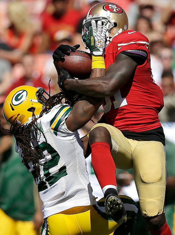 Description of . San Francisco 49ers wide receiver Anquan Boldin catches a pass over Green Bay Packers defensive back Jerron McMillian (22) during the second quarter of an NFL football game in San Francisco, Sunday, Sept. 8, 2013. (AP Photo/Marcio Jose Sanchez)