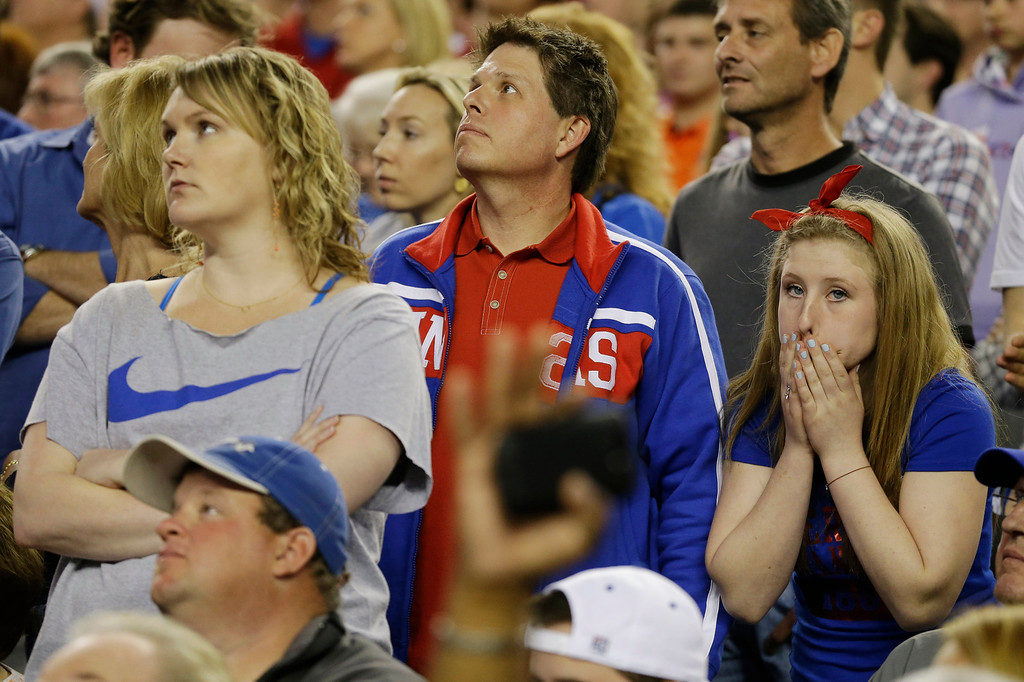Description of . Kansas  fans react in the during overtime of a regional semifinal game against Michigan in the NCAA college basketball tournament, Friday, March 29, 2013, in Arlington, Texas. (AP Photo/Tony Gutierrez)