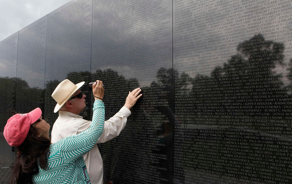. A man touches the Vietnam Veterans Memorial wall, etched with the names of more than 58,000 U.S. servicemen and women who died in the war, in Washington May 23, 2013.  REUTERS/Yuri Gripas