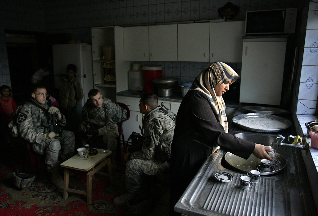 Description of . An Iraqi woman washes dishes as US soldiers from Baker Company 2-12 Infantry Battalion temporarily occupy her home during a patrol in the Dora neighborhood of southern Baghdad, 16 March 2007. Shiite protesters demanded the removal of a US military base from Sadr City in east Baghdad as US commanders reported a surge of attacks on troops in a province near the capital. (DAVID FURST/AFP/Getty Images)
