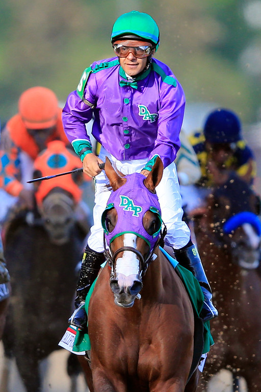 Description of . Jockey Victor Espinoza celebrates atop of California Chrome #5 after crossing the finish line to win the 140th running of the Kentucky Derby at Churchill Downs on May 3, 2014 in Louisville, Kentucky.  (Photo by Rob Carr/Getty Images)