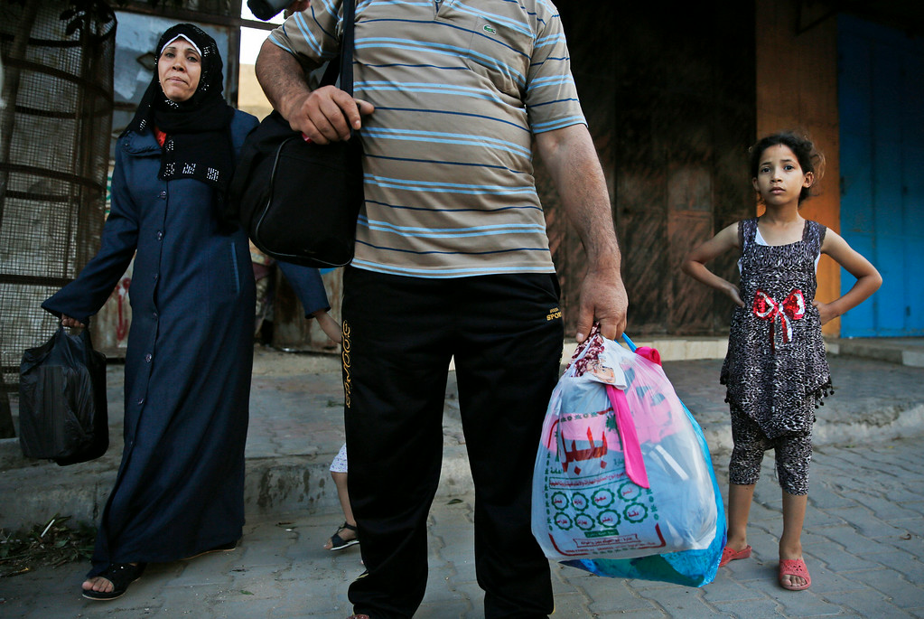 Description of . Palestinians flee their homes in the Shajaiyeh neighborhood of Gaza City, after Israel had airdropped leaflets warning people to leave the area, Wednesday, July 16, 2014. Palestinians flee their home in Gaza City, Wednesday, July 16, 2014. Alongside the air strikes, Israel also ordered tens of thousands of residents of the northern town of Beit Lahiya and the Zeitoun and Shijaiyah neighborhoods of Gaza City, all near the border with Israel, to evacuate their homes by 8 a.m. Wednesday. The warnings were delivered in automated phone calls, text messages and leaflets.(AP Photo/Lefteris Pitarakis)