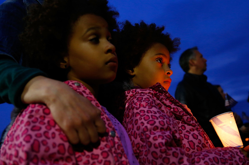 Description of . BOSTON, MA - APRIL 16: Twin sisters hold a candle while listening during the vigil for eight-year-old Martin Richard, from Dorchester, who was killed by an explosion near the finish line of the Boston Marathon on April 16, 2013 at Garvey Park in Boston, Massachusetts. The twin bombings resulted in the deaths of three people and hospitalized at least 128. The bombings at the 116-year-old Boston race resulted in heightened security across the nation with cancellations of many professional sporting events as authorities search for a motive to the violence. (Photo by Jared Wickerham/Getty Images)