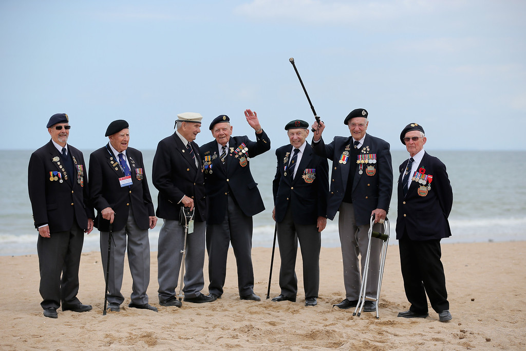 Description of . D-Day veterans (L-R) Wally Beale 90, Dough lakey 94, Bernie Howell 89, Bob Conway 88, George French 88, Gordon Smith 90, and Albert Williams 96,  from the Royal Wootton Bassett Normandy Veterans Association pose for a group photograph on sword Beach after the Royal Artillery Commemoration Parade and service on June 5, 2014 in Hermanville, France.   (Photo by Christopher Furlong/Getty Images)