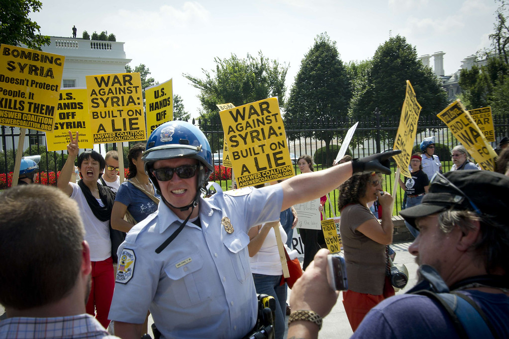 Description of . Demonstrators are directed by a police officer in front of the White House during a rally against a possible US attack on Syria, in Washington, DC on August 31, 2013. US President Barack Obama said Saturday he will ask the US Congress to authorize military action against Syria, lifting the threat of immediate strikes on President Bashar al-Assad's regime. Obama said he had decided he would go ahead and launch military action on Syria, but he believed it was important for American democracy to win the support of lawmakers. MLADEN ANTONOV/AFP/Getty Images