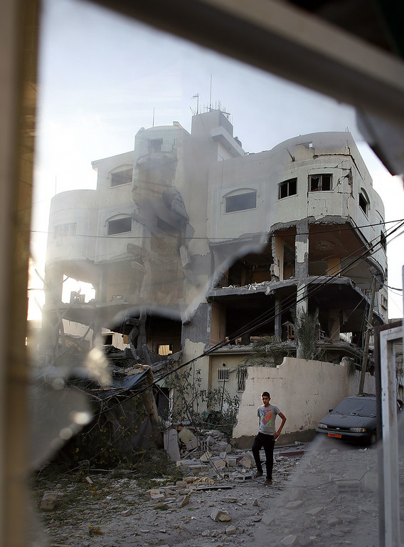 Description of . A Palestinian man walks past the house of senior Hamas official Mahmud al-Zahar after it was destroyed by an overnight Israeli air strike, on July 16, 2014, in Gaza City. New Israeli air and tank strikes in Gaza early today killed several people, medics said, bringing the death toll from Israel's operation in the besieged Palestinian territory to 204. AFP PHOTO / THOMAS COEX/AFP/Getty Images