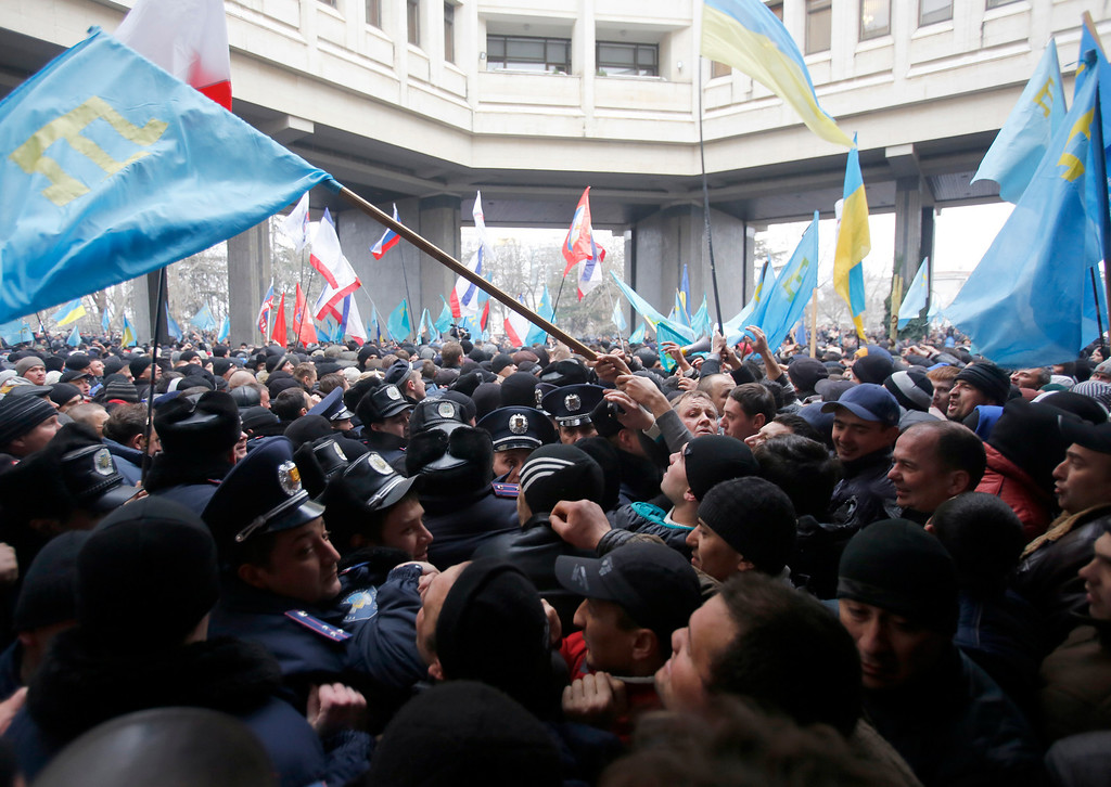 Description of . Crimean Tatars, right clash with police in front of a local government building in Simferopol, Crimea, Ukraine, Wednesday, Feb. 26, 2014. More than 10,000 Muslim Tatars rallied in support of the interim government. That group clashed with a smaller pro-Russian rally nearby. Fistfights broke out between pro- and anti-Russian demonstrators in Ukraine's strategic Crimea region on Wednesday as Russian President Vladimir Putin ordered massive military exercises just across the border. (AP Photo/Darko Vojinovic)