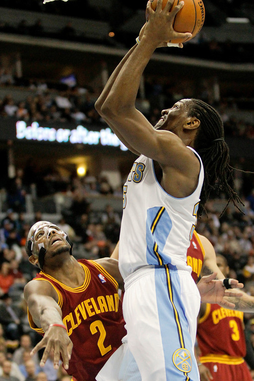 Description of . Denver Nuggets' Kenneth Faried, right, shoots over Cleveland Cavaliers' Kyrie Irving, left, during the first quarter of an NBA basketball game Friday, Jan. 11, 2013, in Denver. (AP Photo/Barry Gutierrez)