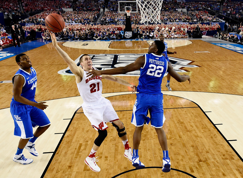 Description of . ARLINGTON, TX - APRIL 05: Josh Gasser #21 of the Wisconsin Badgers takes a shot as Alex Poythress #22 of the Kentucky Wildcats defends during the NCAA Men's Final Four Semifinal at AT&T Stadium on April 5, 2014 in Arlington, Texas. (Photo by Chris Steppig-Pool/Getty Images)