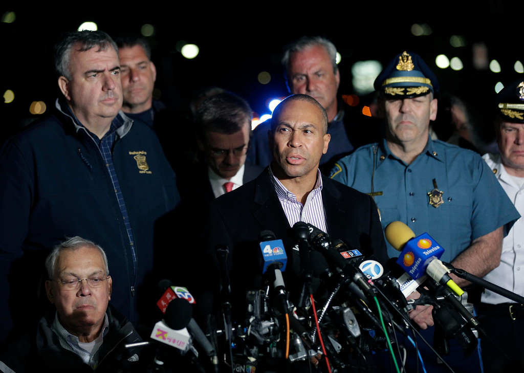 Description of . Massachusetts Governor Deval Patrick, at podium, speaks during a news conference, after the arrest of a suspect of the Boston Marathon bombings in Watertown, Mass., Friday, April 19, 2013. A 19-year-old college student wanted in the Boston Marathon bombings was taken into custody Friday evening after a manhunt that left the city virtually paralyzed and his older brother and accomplice dead.  (AP Photo/Matt Rourke)