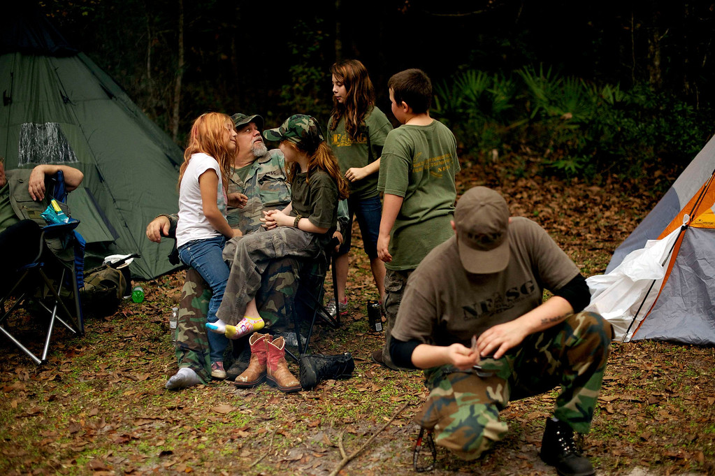 ". Members of the North Florida Survival Group, including leader Jim Foster (2L) relax in their camp as they take a short break from performing land navigation and enemy contact drills during a field training exercise in Old Town, Florida, December 8, 2012.  The group trains children and adults alike to handle weapons and survive in the wild. The group passionately supports the right of U.S. citizens to bear arms and its website states that it aims to teach ""patriots to survive in order to protect and defend our Constitution against all enemy threats\"". Picture taken December 8, 2013.   REUTERS/Brian Blanco"