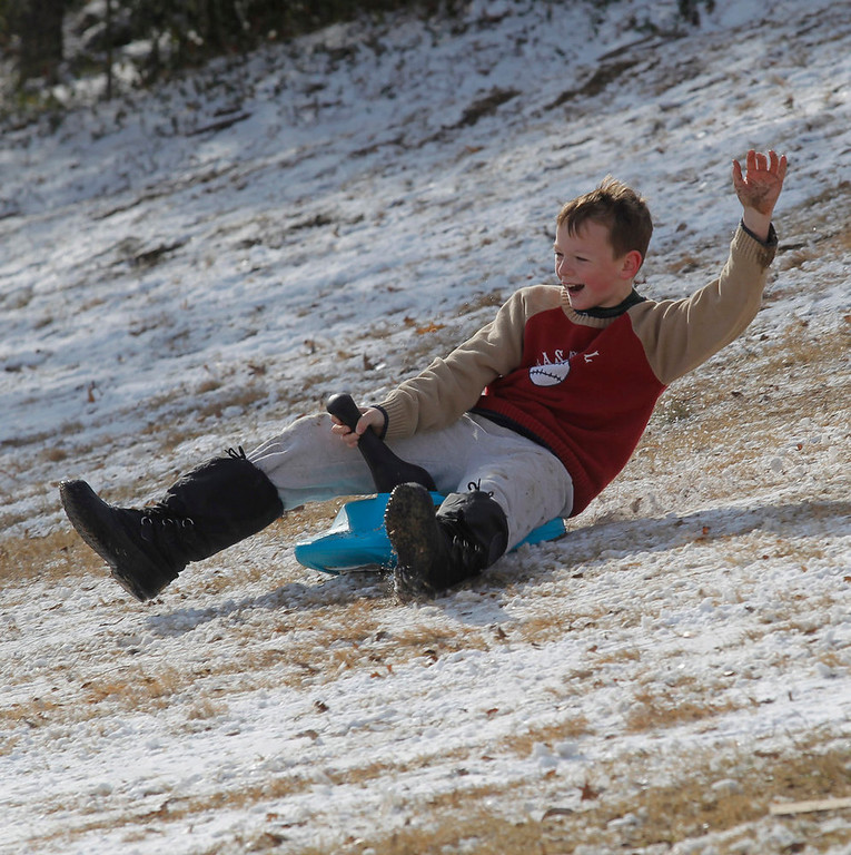 Description of . Jason Buley, 11, slides down a hill in Foster Park on a make shift sled, Wednesday, Dec. 26, 2012, after winter weather covered the area with a layer of snow on Christmas Day. (AP Photo/The Fort Worth Star-Telegram, Rodger Mallison)