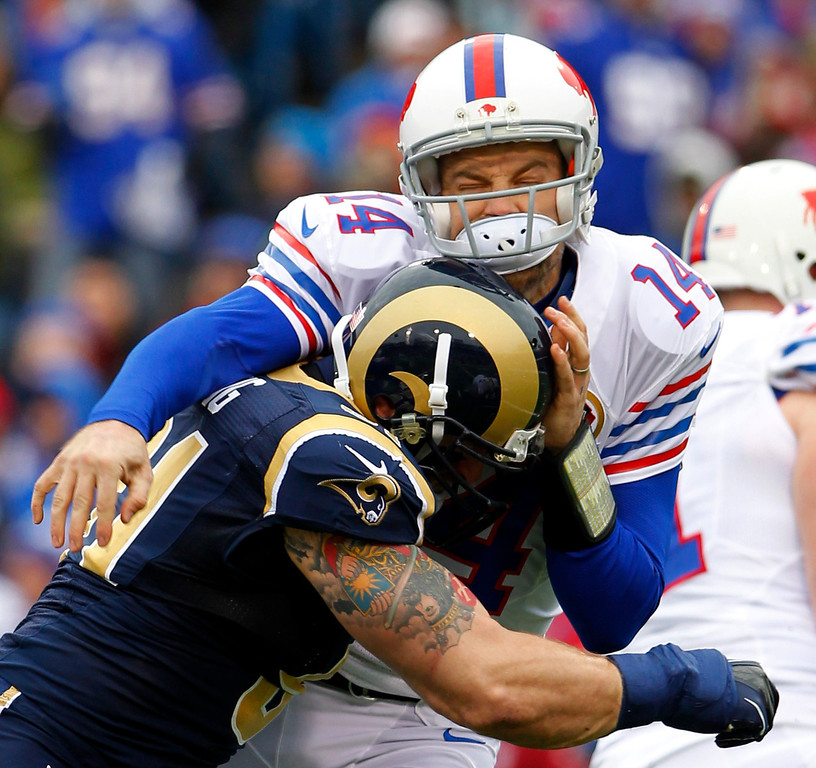 Description of . Buffalo Bills quarterback Ryan Fitzpatrick, right, is hit by St. Louis Rams defensive end Chris Long during the first half of an NFL football game, Sunday, Dec. 9, 2012, in Orchard Park, N.Y. (AP Photo/Bill Wippert)