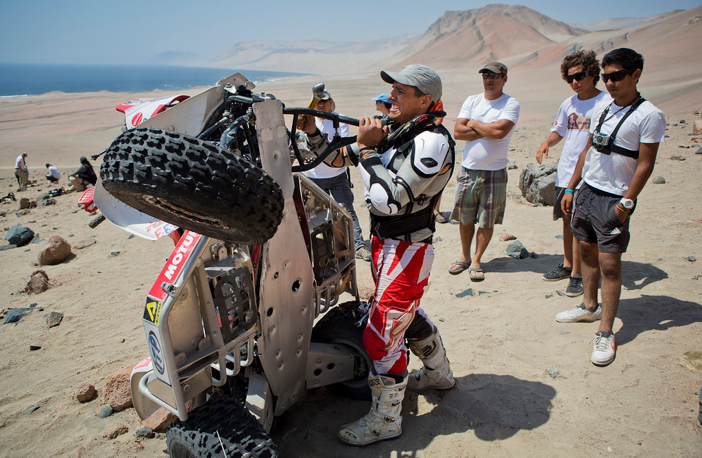 Description of . Honda rider Alexis Hernandez, center, tries to fix the suspension of his quad during the 3nd stage of the 2013 Dakar Rally from Pisco to Nazca, Peru, Monday, Jan. 7, 2013. The race finishes in Santiago, Chile, on Jan. 20. (AP Photo/Victor R. Caivano)