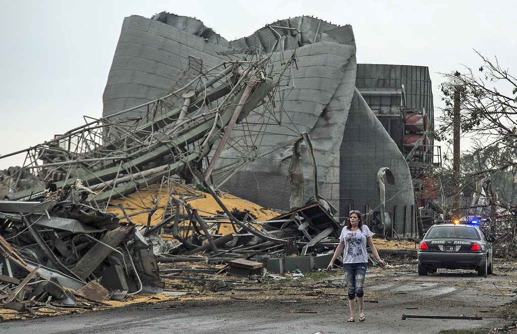 Description of . A woman walks down Black Hills Trail road in Pilger, Neb., Monday, June 16, 2014. At least one person is dead and at least 16 more are in critical condition after two massive tornadoes swept through northeast Nebraska on Monday. (AP Photo/Mark \'Storm\' Farnik)