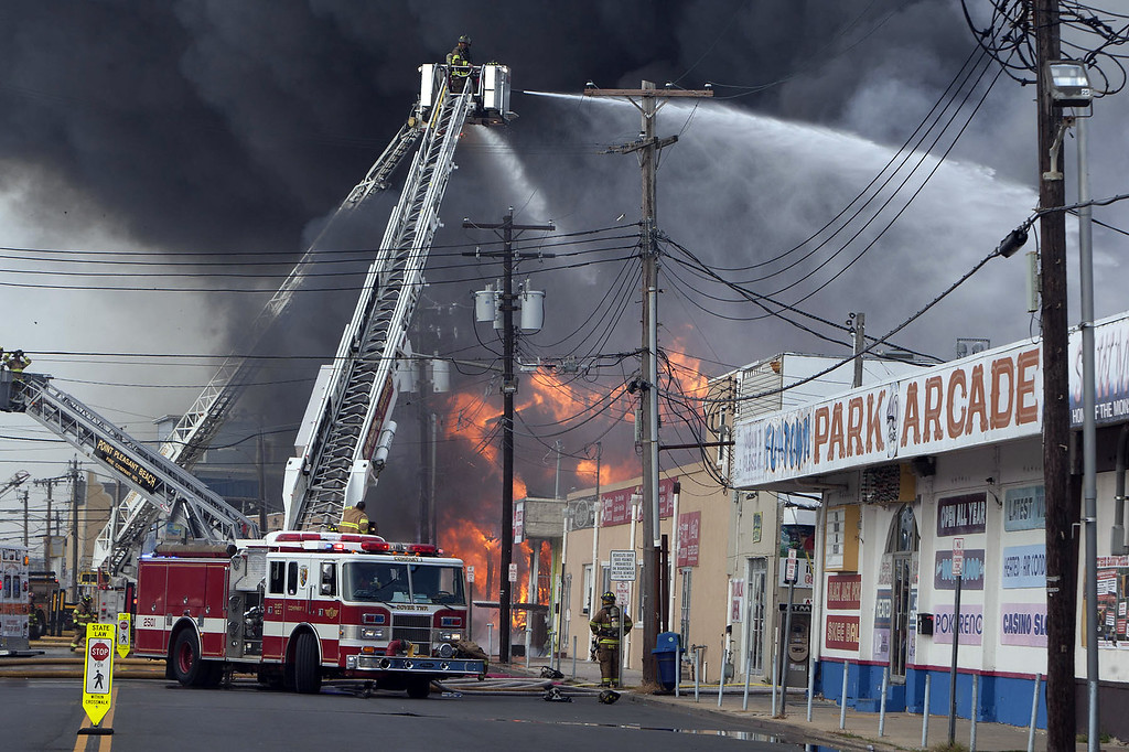 Description of . Firefighters battle a fire on the Seaside Heights, N.J. boardwalk Thursday, Sept. 12, 2013. The fire started in the vicinity of an ice cream shop and burned several blocks of boardwalk and businesses in a town that was still rebuilding from damage caused by Superstorm Sandy. (AP Photo/The Asbury Park Press, Bob Bielk)
