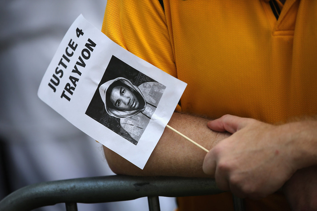 Description of . A demonstrator holds a sign with the likeness of Trayvon Martin while protesting in front of the Seminole County Criminal Justice Center where a jury is deliberating in the trial of George Zimmerman on July 13, 2013 in Sanford, Florida. Zimmerman, a neighborhood watch volunteer, is on trial for the February 2012 shooting death of 17-year-old Trayvon Martin.  (Photo by Scott Olson/Getty Images)