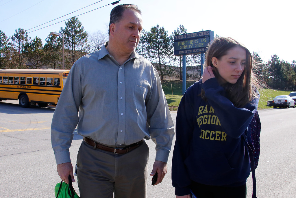 Description of . Jenna Mickel, right, a sophomore at Franklin Regional High School, right, stands with her father, Richard, as she talks with reporters near the school, where several people were stabbed, Wednesday, April 9, 2014, in Murrysville, Pa., near Pittsburgh. The suspect, a male student, was taken into custody and being questioned. (AP Photo/Gene Puskar)