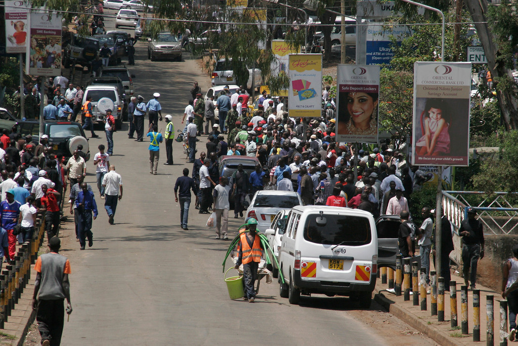 Description of . Crowds gather outside the Westgate Mall, an upscale shopping mall  in Nairobi, Kenya Saturday Sept. 21 2013, where shooting erupted when armed men staged an attack. (AP Photo/Jason Straziuso)