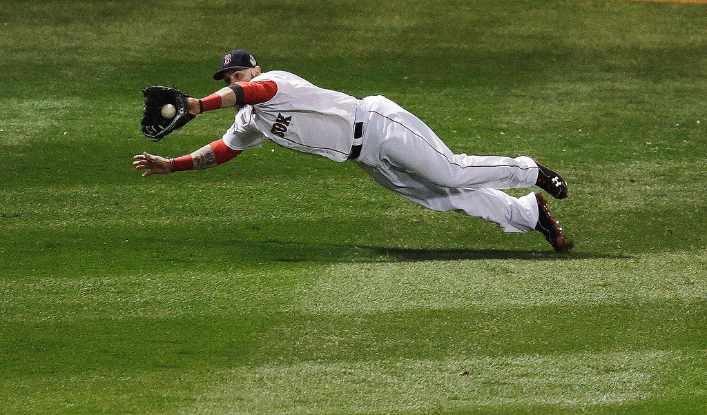 Description of . Boston Red Sox's Jonny Gomes makes a diving catch on a ball hit by St. Louis Cardinals' Matt Adams during the fifth inning of Game 1 of baseball's World Series Wednesday, Oct. 23, 2013, in Boston. (AP Photo/Charles Krupa)