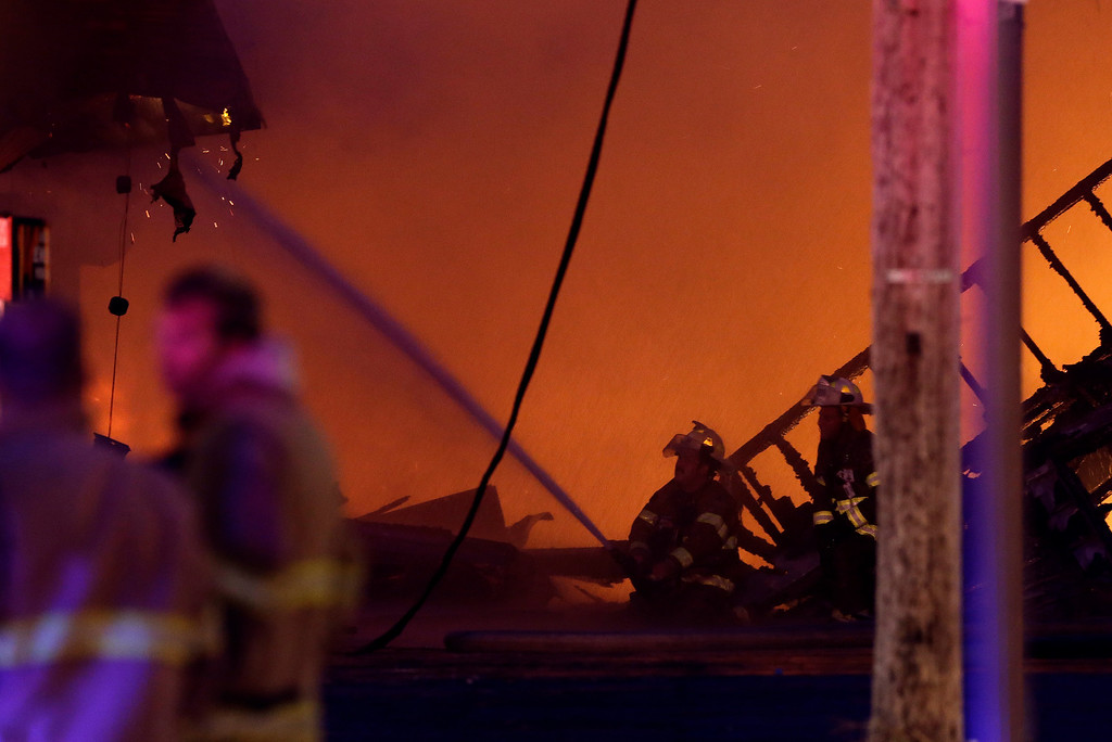Description of . Firefighters battle a blaze in a building at the Seaside Park boardwalk on Thursday, Sept. 12, 2013, in Seaside Park, N.J. The fire began in a frozen custard stand on the Seaside Park section of the boardwalk and quickly spread north into neighboring Seaside Heights. (AP Photo/Julio Cortez)