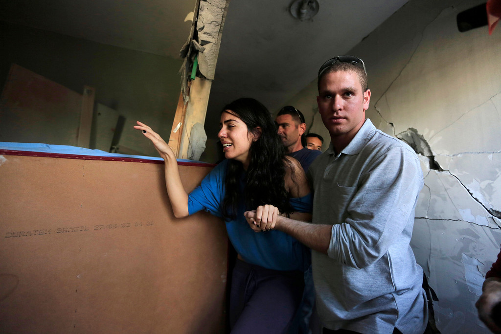 Description of . In this Nov. 20, 2012 file photo, Israelis Sapir, left, and her boyfriend Ron, right, last names not given, walk inside Sapir's home, hit by a rocket fired by militants from Gaza Strip, in the southern city of Beersheba, Israel.  (AP Photo/Tsafrir Abayov, File)