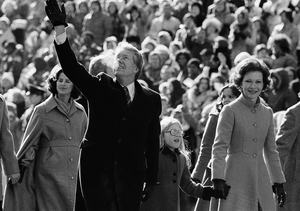 Description of . President and Mrs. Jimmy Carter wave for the crowd along Pennsylvania Avenue and hold the hands of their daughter, Amy. The Carters elected to walk the parade route from the Capitol to the White House following his inauguration in Washington, on Thursday, Jan. 20, 1977. (AP Photo/Suzanne Vlamis)